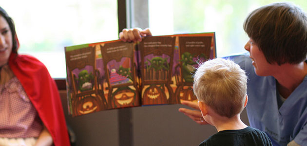 Photo of adult reading a book to a child at Halloween